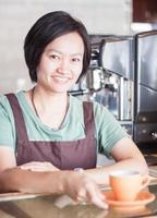 lächelnder asiatischer Barista, der mit Tasse Kaffee aufwirft