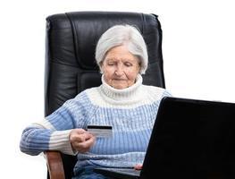ältere Frau, die eine Kreditkarte hält foto