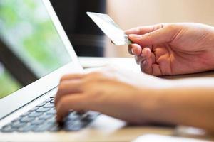 Frau, die Kreditkarte auf Laptop für Online-Einkaufskonzept hält