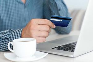 Mann macht Online-Shopping mit Kreditkarte auf Laptop foto
