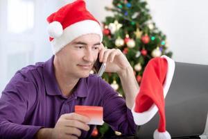 lächelnder Mann mittleren Alters kauft Online-Geschenke für Weihnachten foto