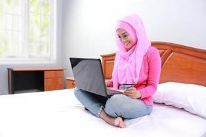 junge muslimische Frau arbeiten mit Laptop auf Bett foto