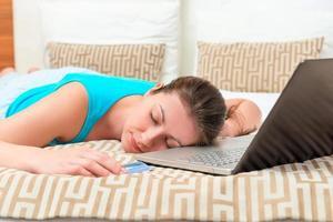 Frau müde vom Online-Shopping im Bett schlafend