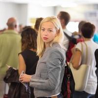 junge blonde kaukasische Frau, die in der Schlange wartet. foto