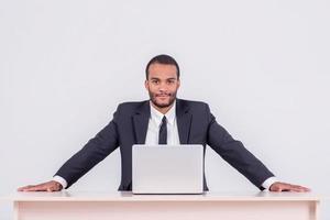 Die Arbeit ist erledigt. lächelnder afrikanischer Geschäftsmann sitzend foto