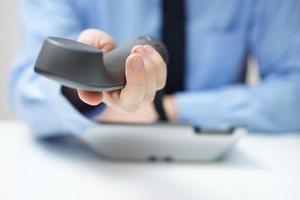 Geschäftsmann bietet Telefonhörer an foto