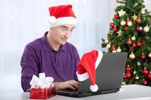 überraschte Senior Santa Claus Mann mit Computer foto