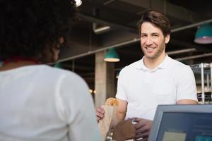 Kunde zahlt ihr Brot an Kellner foto