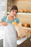 hübsche Kellnerin, die Croissant in Papiertüte steckt foto
