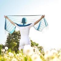 Frau hält einen Schal, der im Wind weht foto