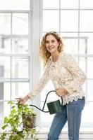 lächelnde Frau, die Pflanze zu Hause wässert foto