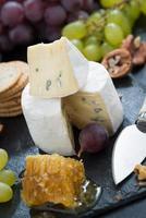 Camembert mit frischem Honig, Trauben und Nüssen, Nahaufnahme foto