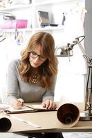 schöne Modedesignerin, die in ihrem Studio arbeitet foto