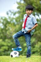 kleiner asiatischer Junge mit Fußball im Park