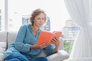 fröhliche blonde Frau sitzt auf ihrer Couch und liest ein Buch foto