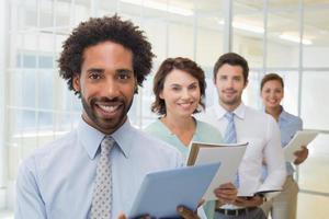Geschäftskollegen halten Notizblöcke und digitales Tablet in Reihe