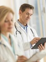 männlicher Arzt mit digitaler Tablette im Krankenhaus