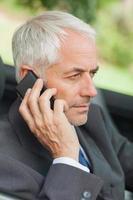 ernsthafter Geschäftsmann am Telefon, der Cabriolet fährt foto