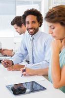 lächelnder Geschäftsmann mit Kollegen im Treffen im Büro foto