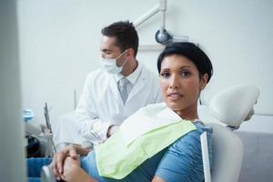 ernsthafte Frau, die auf zahnärztliche Untersuchung wartet foto