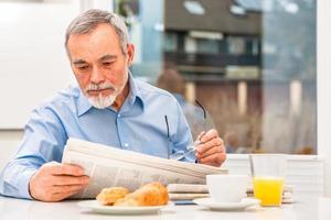 älterer Mann mit einer Zeitung foto