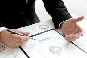 Geschäftsmann, der mit Grafiken und Tabellen im Büro erklärt foto