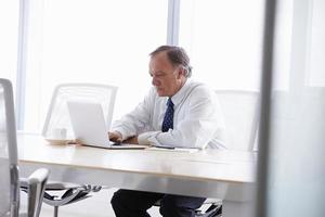 älterer Geschäftsmann, der am Laptop am Sitzungssaaltisch arbeitet foto