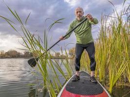 Steh auf und paddle auf einem See foto
