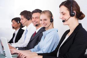 Geschäftsleute, die Headset tragen, das im Büro arbeitet