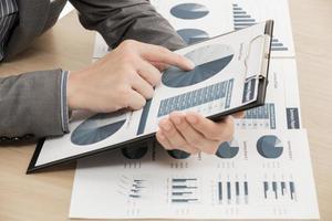 Geschäftsbericht und Mannhand mit Stift foto