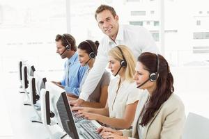 Geschäftsleute mit Headsets, die Computer im Büro verwenden foto