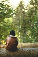 junge auf baumstamm sitzend gehört in die ferne foto