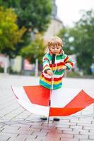 glücklicher kleiner Junge mit gelbem Regenschirm und bunter Jacke outoo foto