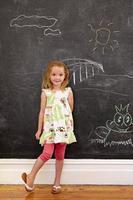 unschuldiges kleines Mädchen, das mit Kreidezeichnungen zu Hause steht foto