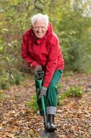 älterer Mann mit Spaten im Garten foto