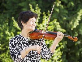 ältere asiatische Frau, die Geige im Freien spielt foto