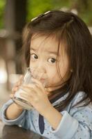 asiatisches süßes kleines Mädchen, das Milch trinkt