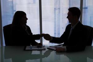 Geschäftsleute, die am Schreibtisch Händeschütteln foto