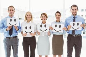 Geschäftsleute, die glückliche Smileys im Amt halten foto