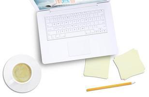 weißer Laptop und Kaffeetasse auf Teller, Draufsicht foto