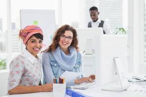 Porträt der lächelnden Teamarbeit, die am Schreibtisch sitzt foto