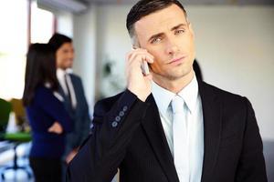 selbstbewusster Geschäftsmann, der am Telefon spricht foto
