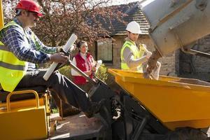 männliche Bauarbeiter werden von weiblichen Organisatoren beobachtet foto