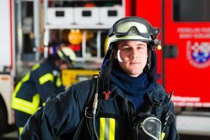 junger Feuerwehrmann posiert für Foto vor Feuerwehrauto