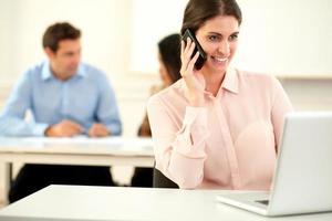 hübsche Geschäftsfrau spricht auf ihrem Handy foto