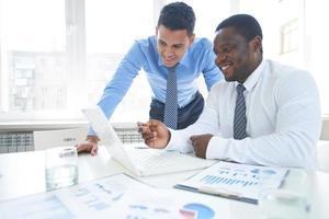zwei Geschäftsleute, die an einem Laptop in einem Konferenzraum arbeiten