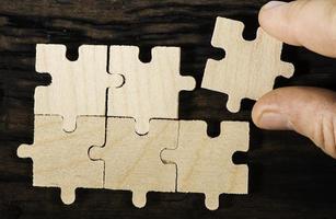 Holzpuzzle auf dunklem Hintergrund.