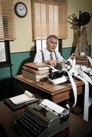 verwirrter Retro-Buchhalter, der Rechnungen prüft foto