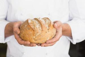 Bäcker zeigt frisch gebackenen Laib foto