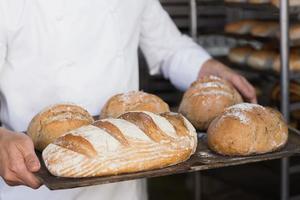 Bäcker hält Tablett mit Brot foto